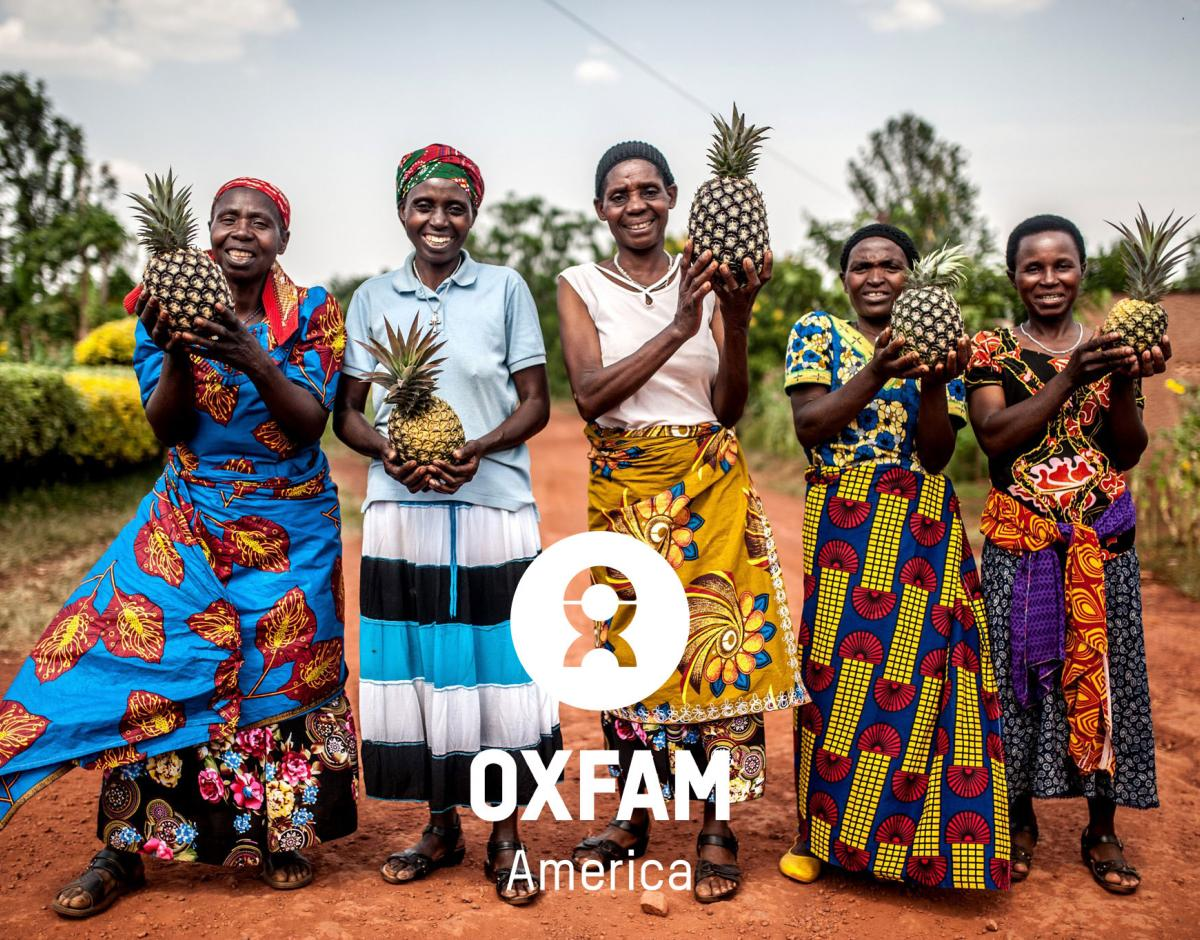 Women smiling outside of a pineapple cooperative in Rwanda.