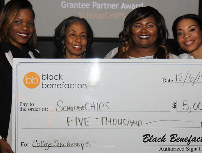 four women holding giant donation check